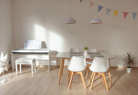 Modern white interior with eating table and e-piano
