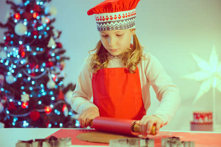 Pretty little girl decoraiting christmas cookies of different forms at home with christmas tree on background Фото со стока