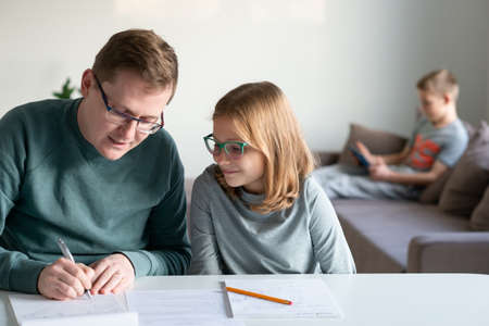 Young father helping his children with homeschooling during covid-19 lockdown