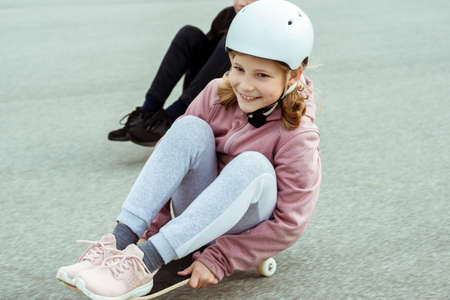Happy teenagers boy and girl having fun skateboarding in street in helmets