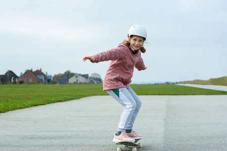 Adorable teenage girl drives with skateboard on smooth asphalt in white helmet Фото со стока