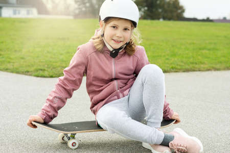 Portrait of adorable teenager girl having fun during skateboarding on smooth asphalt