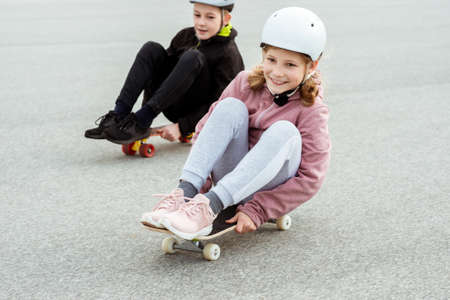Happy teenagers boy and girl having fun skateboarding in street in helmets Standard-Bild