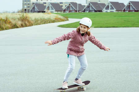 Adorable teenage girl drives with skateboard on smooth asphalt in white helmet Standard-Bild