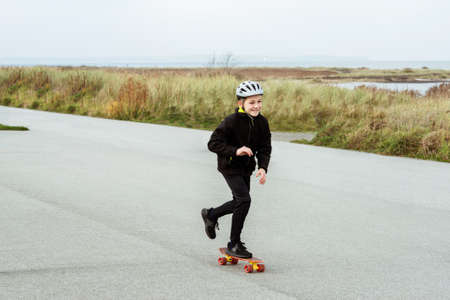 Happy teenager boy practice skateboarding on smooth asphalt