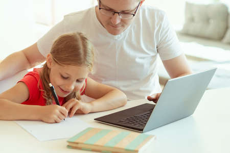 Young father at home office helping his teen daughter with online learning at homeschooling