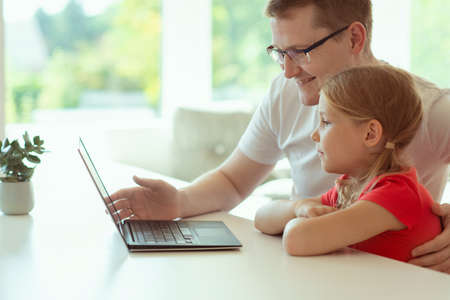 Happy young father with cute doughter learning together online at homeschooling