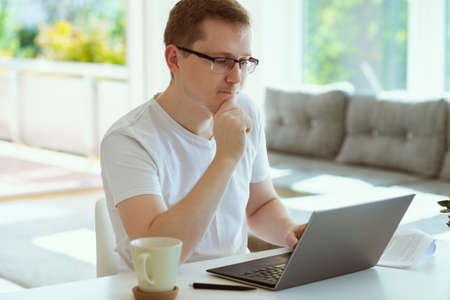 Portrait of serious young man working online with laptop at home, holding paper sitting at office desk Фото со стока