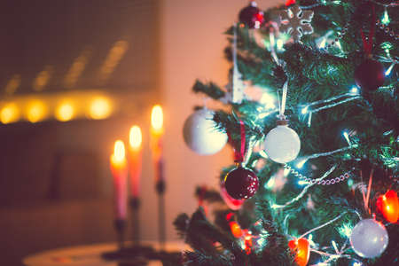 Close up photo of christmas tree decorated with balls, red hearts in darkness but with christmas lights at new years eve
