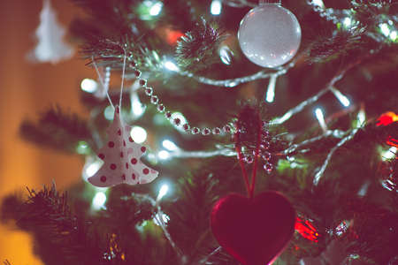 Close up photo of christmas tree decorated with balls, red hearts in darkness but with christmas lights at new years eve Banque d'images