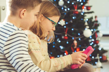 Happy teen siblings children or friends playing games with tablet on sofa near christmas tree at home