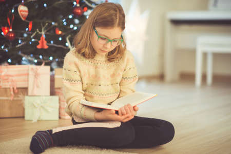 Portrait of pretty little child girl reading book sitting near decorated christmas tree