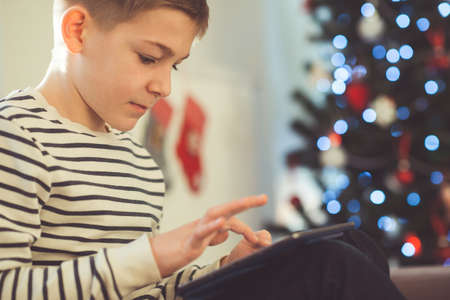 Teenager boy playing or studing with laptop near decorated christmas tree in living room at home