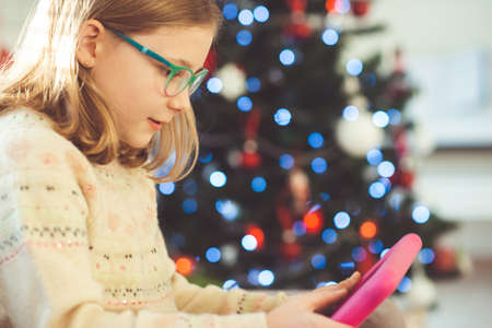 Cute little child girl playing with tablet sitting near decorated christmas tree