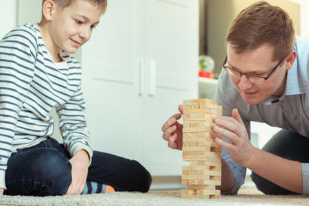 Happy young father playing with his cute son with wooden blocks at home