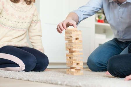 Happy young father playing with his cute daughter with wooden blocks at home