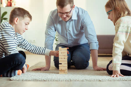 Young happy father playing with his two cute children with wooden blocks at home