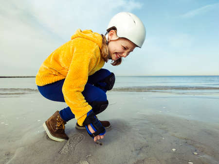 Portrait of pretty teenager child girl in yellow pullover, helmet and inline protective equipment posing on Baltic sea beach