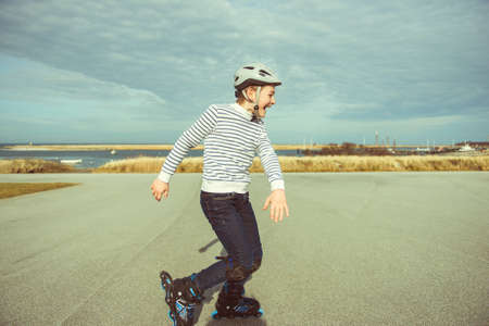 Happy teenager boy in helmet, inline skates and safety equipment is happy learning skating sunny day in summer Stockfoto