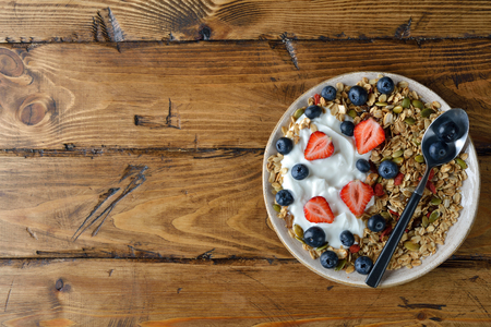 Muesli with strawberries and blueberries on a brown background