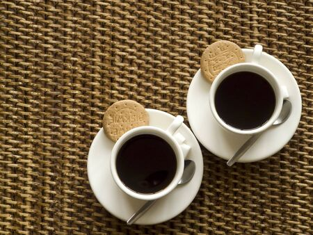 Topview of two cups of coffee with biscuits