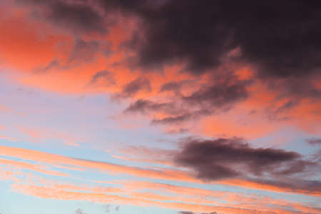 Blue and red colors of evening clouds, whimsical pattern at sunset 스톡 콘텐츠