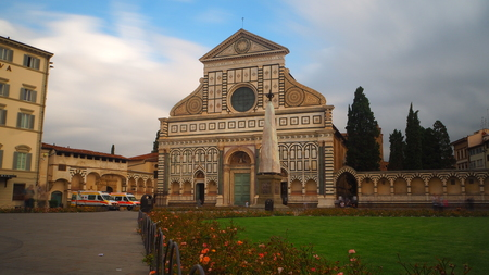 Long exposure of the church of Santa Maria Novella in Florence. The sky has some clouds and there are many tourists in the square in front of it. Editorial