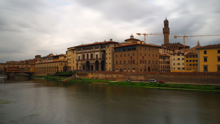 View of the museum on the bank of the Arno river. The autumn sky is leaden and very dark.