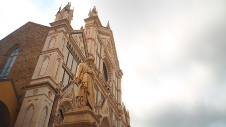 Dante Alighieri with a view of the church of Santa Croce in Florence. The sky is covered by many clouds.