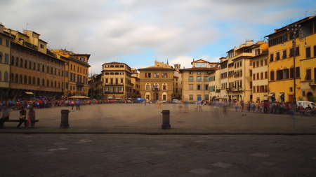 Long exposure of Piazza di Santa Croce, in front of the church of the same name. There are many tourists and the sky is very cloudy. Editorial