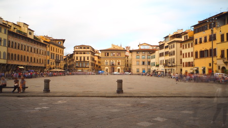Long exposure of Piazza di Santa Croce, in front of the church of the same name. There are many tourists and the sky is very cloudy. Banco de Imagens