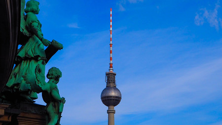 February 2018: view of the Berlin TV Tower from the Berliner Dom. There are two statues that seem to look at the tower. February 2017 in Berlin