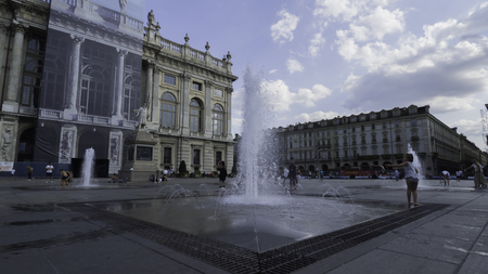 August 2018: Fountains throw splashes from the ground in front of the Palazzo Madama museum, with the fa?ade in reconstruction. Late afternoon of a warm and sunny day. August 2018 in Turin Foto de archivo - 109867359