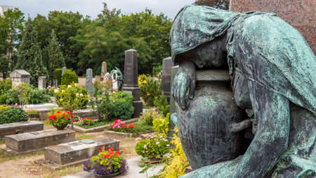 Nuremberg 2019. Bronze statue of a weeping woman, aged by time, on a burial in the monumental cemetery of St. John's. August 2019 in Nuremberg.