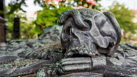 Nuremberg 2019. Skull statue with bronze snake, aged by time, on a burial in the monumental cemetery of St. John's. August 2019 in Nuremberg.