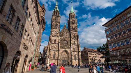 Nuremberg 2019. Tourists or ordinary citizens strolling in front of the main building of the Cathedral of St. Lorenz, or Lawrence. We are a sunny summer morning. August 2019 in Nuremberg Editorial