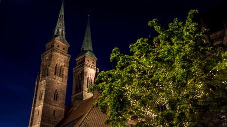 Nuremberg 2019. Illuminated tree and towers of the Church of San Sebaldo. We are on a warm summer night. August 2019 in Nuremberg