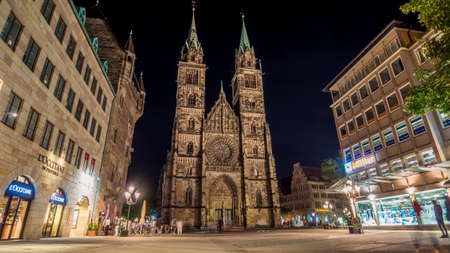 Nurnberg 2019. Tourists walking in the square in front of Saint Lorenz Kirche. We are on a clear night. August 2019 in Nurnberg.