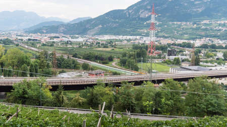 Trento 2019. Highway and local road near train. In the foreground a vineyard is visible. August 2019 Trento Editorial
