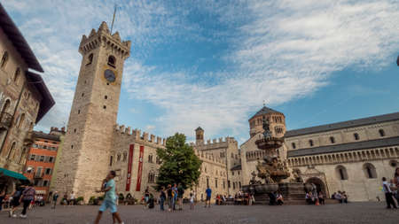 Trento 2019. Tourists and passersby cross Piazza Duomo near the Triton Fountain. We are on a warm but cloudy summer day. August 2019 Trento Editorial