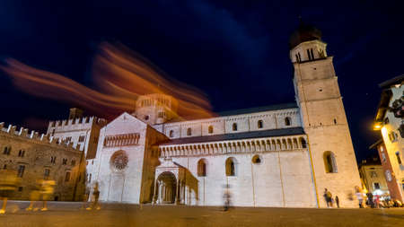 Trento 2019. Night view, in long exposure, of tourists and passersby crossing Piazza Duomo near the Triton Fountain. We are on a warm but cloudy summer night August 2019 Trento Editorial