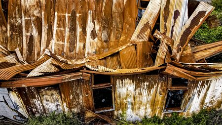 Iron shed, rusty, fallen under the weight of time and weather. Foto de archivo
