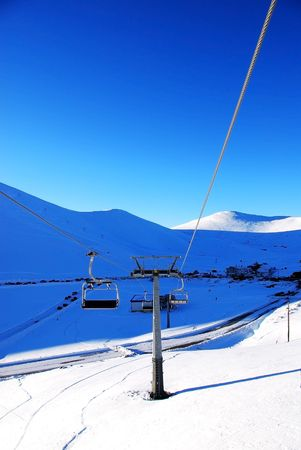 riding a ski chairlift under a clear blue sky photo