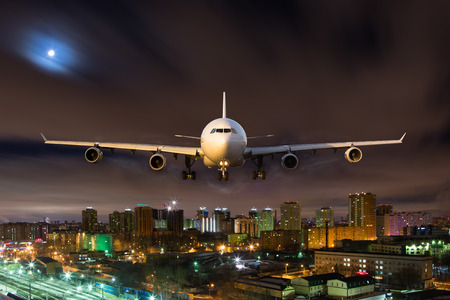 Aircraft flying in moonlight over the night city. Airplane front view. Archivio Fotografico