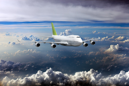 White passenger plane in flight. Aircraft flies high over clouds. Archivio Fotografico