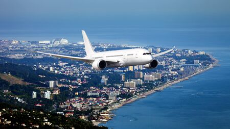 The passenger plane in flight. Aircraft flies high above the coastal city.