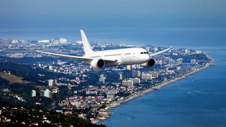 The passenger plane in flight. Aircraft flies high above the coastal city.