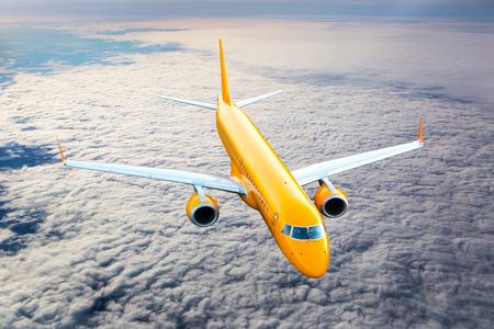 Orange passenger plane in flight. Aircraft flies high above the clouds.