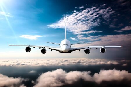 White passenger aircraft in the sky. Airplane flies high over the clouds.