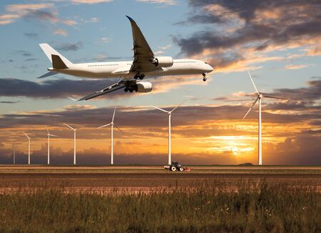 Passenger plane takes off and climbs above the farm field and wind electric generators. Aircraft fly in the bright sunset sky.